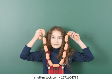 Schoolgirl near green school board. Young playful girl hold the chain of sausages on green school board. High resolution photo.