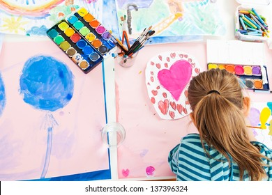 Schoolgirl painting with water color - top view
