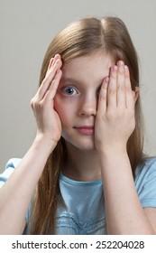 Schoolgirl peeping through hand with one eye over grey background