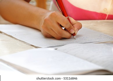 schoolgirl with pen writing down in notebook homework