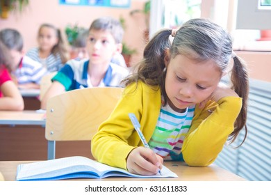 schoolgirl with pen writing in a notebook in classroom