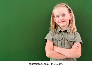 schoolgirl portrait near the blackboards, looking at the camera