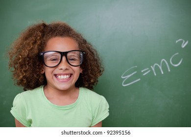 Schoolgirl posing with the the mass-energy equivalence formula on a blackboard
