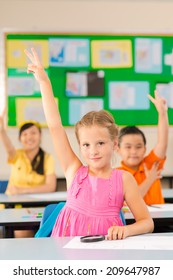 Schoolgirl raising hand and showing two fingers at a lesson