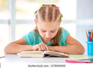 Schoolgirl reading book in light classroom