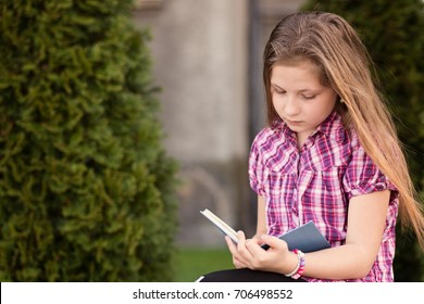 Schoolgirl reading a book outdoors near school. Child reading