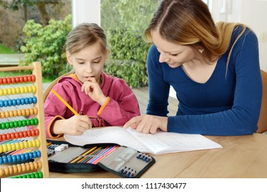 Schoolgirl receives tutoring and help with homework by tutor