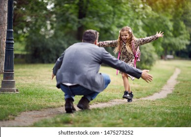 schoolgirl running to dad to give him a hug after school