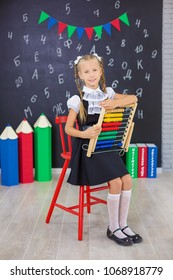 The schoolgirl in school uniform with books on russian Math,Litrature & Russian and textbooks is on a light gray background. Back to school. The new school year. Child education concept