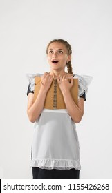 Schoolgirl in school uniform and laptop in hands. beautiful playful teenagers in a festive dress back to school on a white background. start of classes. she opened her mouth in surprise emotion