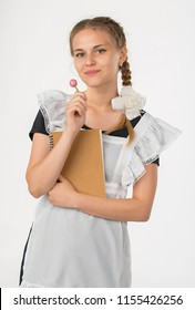 A schoolgirl in school uniform and a notebook in hands. the girl is ready to go to school. beautiful playful teenagers in festive dress back to school on white background. schoolgirl sucks lollipop