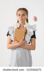 A schoolgirl in school uniform and a notebook in hands. the girl is ready to go to school. beautiful playful teenagers in festive dress back to school on white background. schoolgirl blowing a bubble