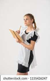 A schoolgirl in school uniform and a notebook and pencil in hands. beautiful playful teenagers in festive dress back to school on white background. the girl writes in a notebook