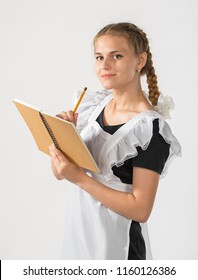 A schoolgirl in school uniform and a notebook and pencil in hands. the girl is ready to go to school. beautiful playful teenagers in festive dress back to school on white background. start of classes