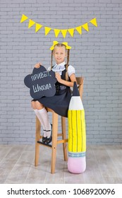 The schoolgirl in school uniform with small black board on russian written - Hello School, is on a light gray background. Back to school. The new school year. Child education concept
