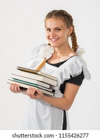 Schoolgirl in school uniform, a stack of books in hands. beautiful playful teenagers in a festive dress back to school on a white background. cheerful schoolgirl. emotion of joy. successful learning
