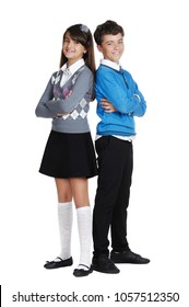 Schoolgirl and a schoolboy in formal outfit standing back to back
