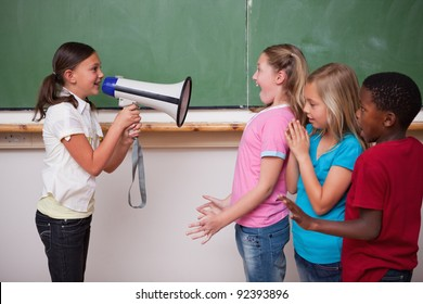 Schoolgirl screaming through a megaphone to her classmates in a classroom