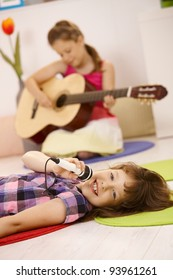 Schoolgirl singing into microphone, smiling at camera, friend playing guitar in background.?