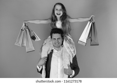 Schoolgirl sits on dads shoulders. Shopaholics, childhood and family concept. Daughter and father with pink and red packages. Girl and man with smiling faces hold shopping bags on blue background