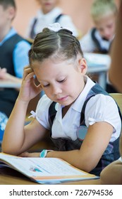 schoolgirl sits at a school desk at a lesson at school