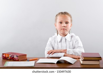 schoolgirl sits at a school desk,  looking at the camera