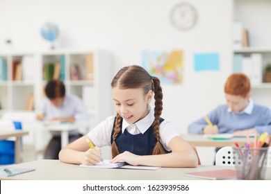 Schoolgirl sitting at desk and making notes in her notebook she working during a lesson at school - Shutterstock ID 1623939586