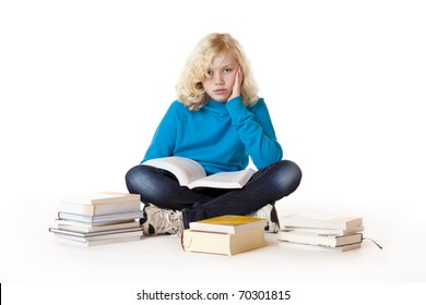 Schoolgirl sitting frustrated on floor and learns with study books.Isolated on white background.