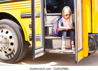 Schoolgirl sitting in school bus and reading the book. Back to school or education concept.