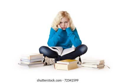 Schoolgirl sitting tired and frustrated on floor and learns with study books.Isolated on white background.