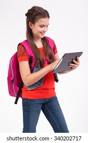 schoolgirl with a smile on his face standing on a white background with a backpack on his shoulders and tablets in the hands of.
