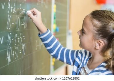 Schoolgirl standing near blackboard with formula