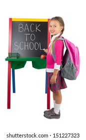 """A schoolgirl standing next to the blackboard with the """"Back to School"""" message on it, isolated"""
