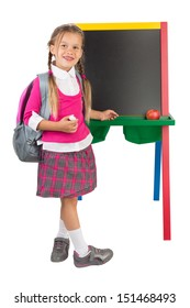 A schoolgirl standing next to the blank blackboard, isolated