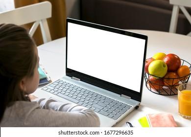 Schoolgirl studying at home using laptop. Home school, online education, home education, quarantine, coronavirus concept. Mockup concept.