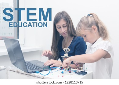 Schoolgirl studying with a teacher robotics, collects arduino robot and programs it on a laptop. Workshop. Stem education. Technology. Science. Scratch.
