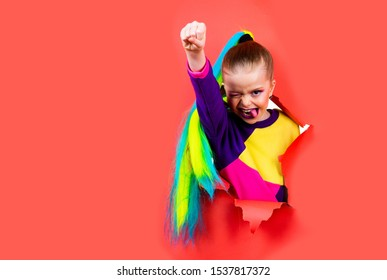 Schoolgirl superhero concept. Brave girl is breaking through color paper wall. Kid hand squeezed into a fist. Trendy clothes and hairstyle ponytail. Girl ready to school. Digital native generation