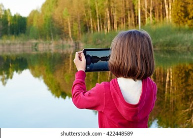 Schoolgirl taking a picture using digital tablet on the lake shore