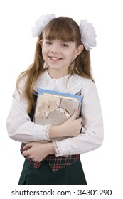 Schoolgirl with textbook. Portrait of smiling, little girl in school uniform. Little pupil is going to school. Isolated over white background.