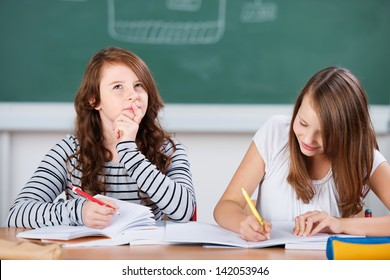Schoolgirl thinking during an school exercise while her classmate writes in the notebook