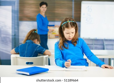 Schoolgirl thinking while filling out test at class, teacher standing in background.