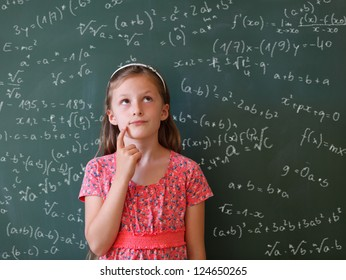 a schoolgirl thoughtful  in front of a blackboard with many mathematical formulas
