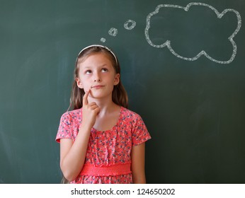 a schoolgirl thoughtful  in front of a blackboard with a thought balloon