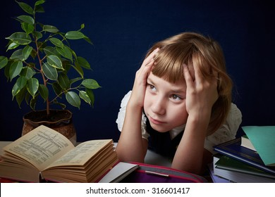 Schoolgirl tired of doing difficult homework. She wants to play with her friends in the yard, but you need to do your homework.