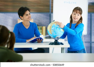 Schoolgirl touching globe in class, teacher smiling holding workbook.