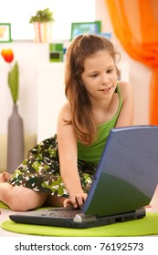 Schoolgirl using laptop at home, sitting on floor, smiling.?