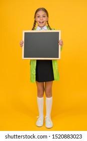 Schoolgirl wear raincoat hold blank chalkboard copy space. Waterproof fabric for comfort. Rainproof accessory. Waterproof clothes. Kid girl happy wear raincoat. Waterproof cloak. Weather forecast.