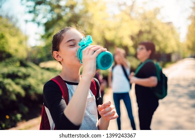 Schoolgirl wearing red backpack drinking water at schoolyard on a sunny day