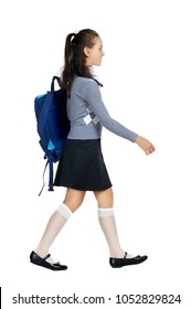 Schoolgirl wearing rucksack walking against white background side view picture