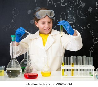 schoolgirl in white gown doing experiments with liquids in chemistry lab